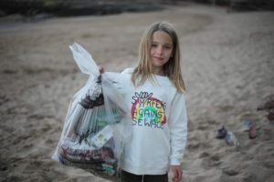 Child holding back of trash found on the beach