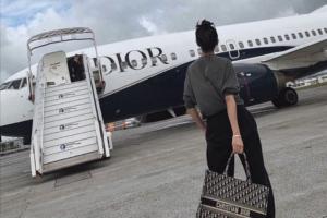 Women holding Dior bag while walking onto Dior airplane
